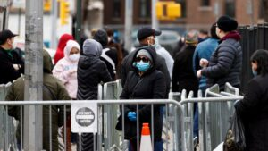 Several people wait to enter a medical check-up and get a coronavirus test, on April 14, 2020, at the Elmhurst Hospital Center in Queens, in New York (USA).